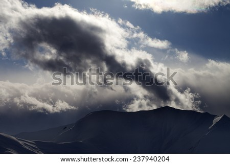 Evening dark mountain and sunlight clouds. View from ski slopes. Caucasus Mountains, Georgia, ski resort Gudauri.