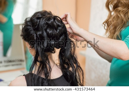 evening hairstyle. brunette doing hairdresser and styling in barber salon - stock photo