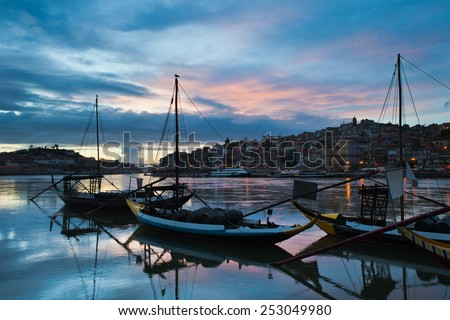 Evening in the city of Porto, Portugal. Rabelo traditional Portuguese cargo boats with wine barrels on Douro river and old city skyline. - stock photo