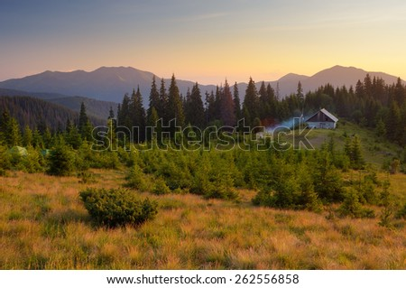 Evening landscape. The light of the setting sun. Wooden house in the mountains. Carpathians, Ukraine, Europe - stock photo
