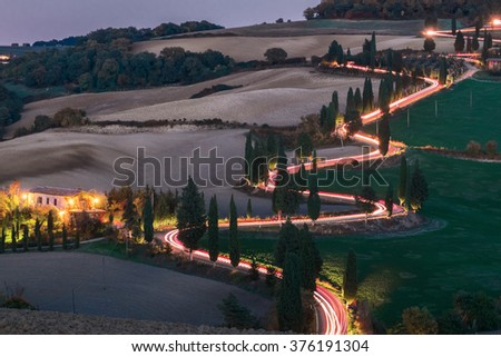 Evening landscapes of Tuscany with traces of car headlights - stock photo