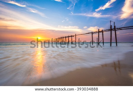 Evening light during sunset on the sea with an old wooden bridge.