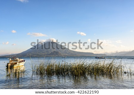Evening light on boats & two volcanoes, Atitlan & Toliman, at Lake Atitlan, Guatemala. - stock photo