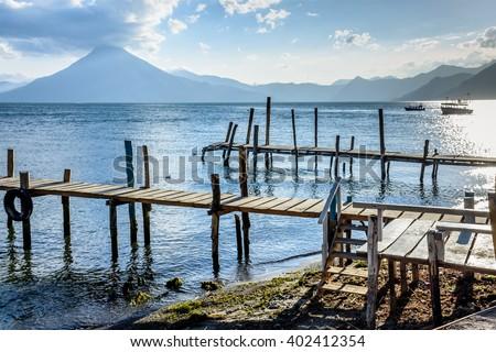 Evening light on jetties on Lake Atitlan with San Pedro volcano behind, Guatemala - stock photo