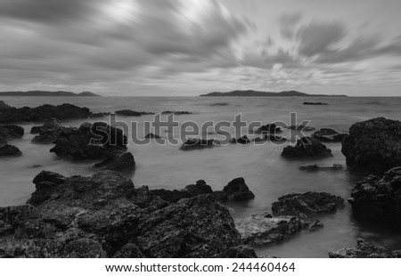 Evening light sunset sea waves splashing rocks black and white tone. - stock photo