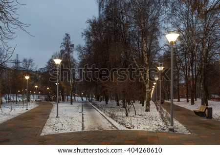 Evening lighting in winter urban. Long walkway with street lamps. City lights and illuminators. Russia, Moscow. - stock photo