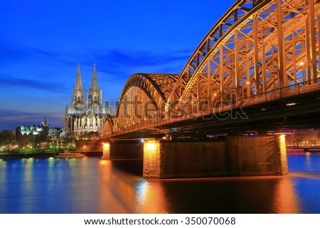 Evening lights illuminate distant Cathedral and iron bridge across Rhine river, Cologne, Germany