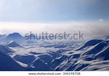 Evening mountains in mist. Caucasus Mountains, Georgia, view from ski resort Gudauri. - stock photo