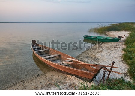 Evening on the lake, fishing boats on the shore