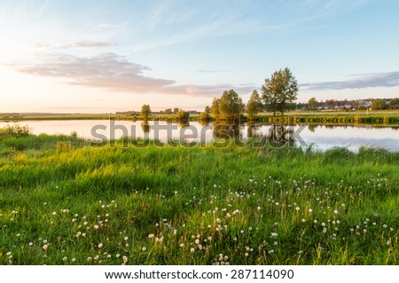 Evening on the river with a field of dandelions, Russia, Ural Mountains - stock photo