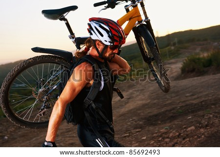 Evening outdoor sport shooting man with bike - stock photo