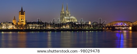 Evening panorama of Cologne with Great St. Martin Church, Cologne Cathedral and Hohenzollern Bridge from bank of the Rhine river, Germany - stock photo