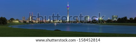 Evening panorama of Dusseldorf with Rheinturm TV tower from the bend of Rhine river, Germany - stock photo