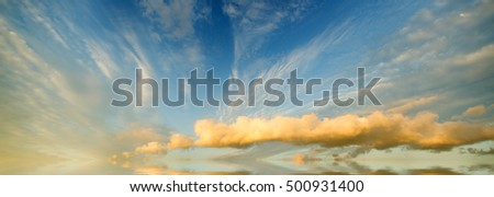 evening panoramic landscape, amazing clouds lit by the rays of the setting sun. The skies at sunset reflected in the sea waves