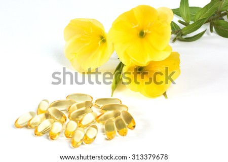 Evening primroses near yellow gelatin capsules on white background
