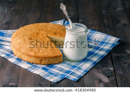 Evening relax concept. Jar of yogurt and pie on table - stock photo