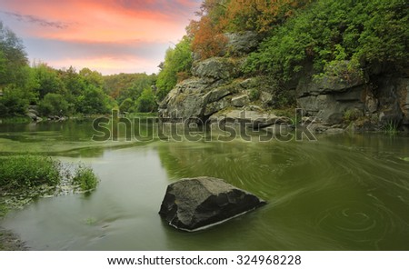 Evening scene on rocky river shore - stock photo