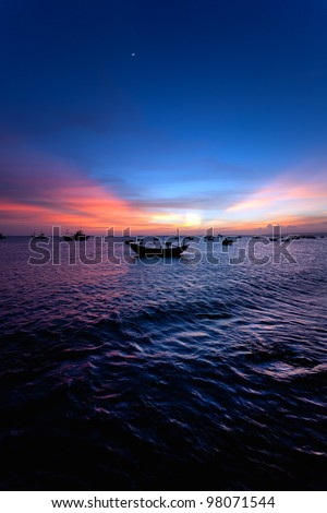 Evening sea decline with boats and the moon - stock photo