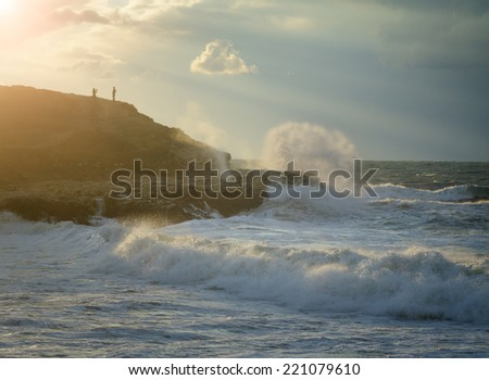 Evening seascape . Storm in ocean with big windy waves. Silhouettes of a peoples on a rock. Nature composition on a background blue sky with clouds sunset. - stock photo