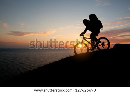 evening silhouette of a man coming down from the tourist mountain bike - stock photo