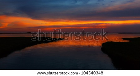 Evening sky over peaceful lake lake and land contours - stock photo