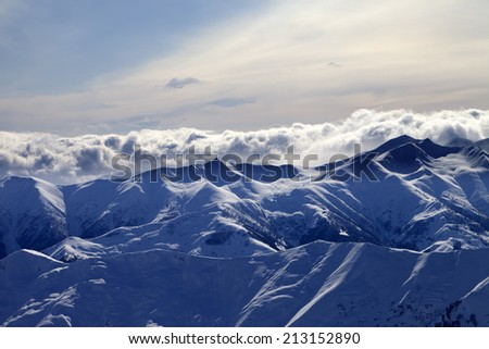 Evening snowy mountains and sunlight clouds. Caucasus Mountains, Georgia, view from ski resort Gudauri. - stock photo