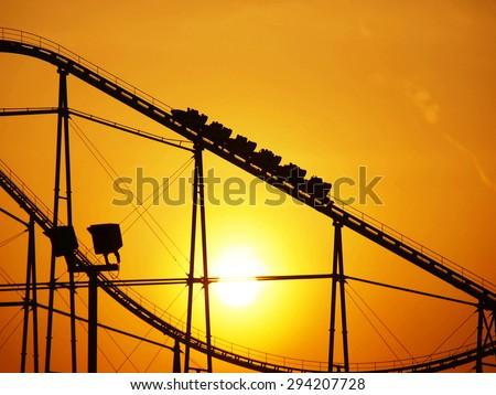 Evening sun and roller coaster - stock photo