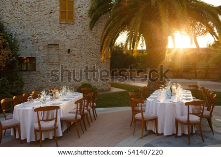 Evening sun illuminates dinner tables standing under  the palm