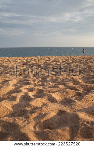 Evening sun on mediterranean beach sand.
