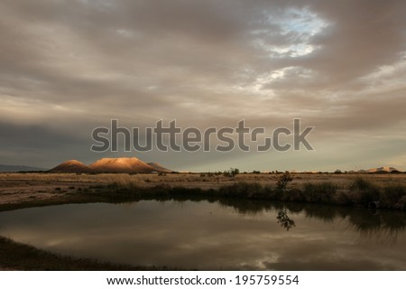 Evening sun spotlights hill top in orange color, and soft gray cirrostratus reflects in water/Orange Sunlight on Hill Top with  Gray Cloud Layers and Sun Rays /Cloudy twilight landscape over hills  - stock photo