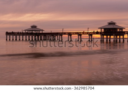 Evening sunset ight on the fishing pier in Fort Myers Beach, Gulf of Mexico Coast, Florida. - stock photo