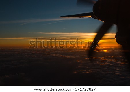 Evening sunshine light with clouds visible. Evening sky Through glass window on airplane and overlooking propeller for transport, business aviation and vehicles concept