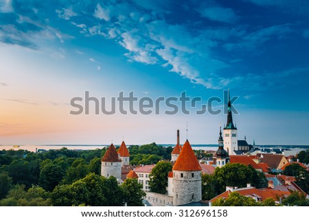 Evening Tallinn's (Estonia) Old Town Cityscape at sunset, clear blue sky. One can see the spiers of St. Nicholas Church and towers, surrounded by a park. - stock photo
