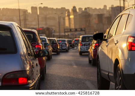 Evening traffic. Drivers who wait in traffic to go home from work at the end of the day. The evening sun is reflected over the cars.  A close-up view of cars. It goes a way between high buildings.  - stock photo