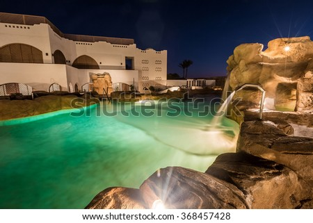 Evening view for buildings behind swimming pool in night illumination  - stock photo