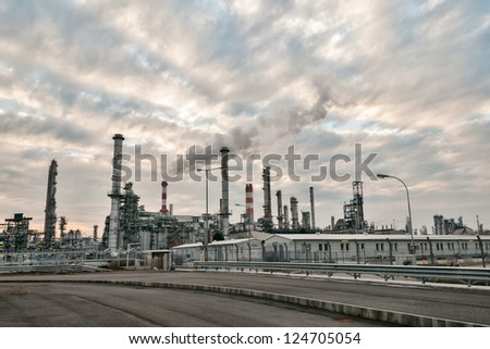 evening view of an oil refinery with cloudy sky and smoking chimneys - stock photo