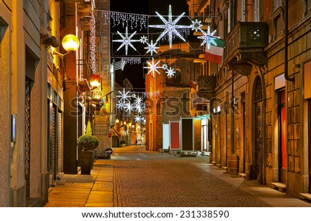Evening view of cobblestone street in old town of Alba with illuminations and decorations for Christmas and New Year celebrations in Piedmont, Northern Italy. - stock photo