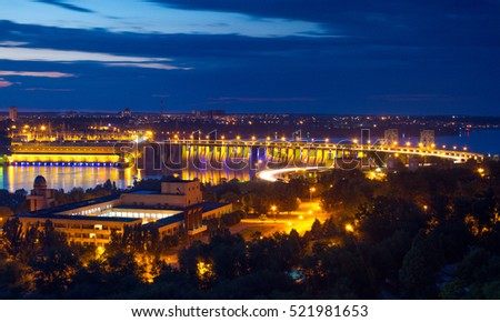 Evening view of Dneproges dam with hydroelectric power station illuminated in blue and yellow colors, Dnieper river, Zaporozhye, Ukraine