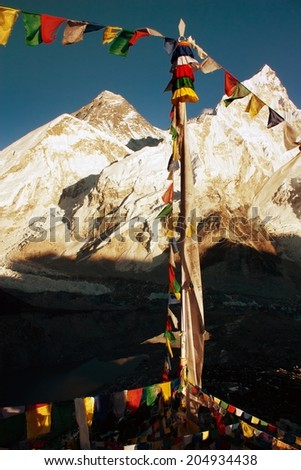 evening view of Everest with buddhist prayer flags from kala patthar and blue sky - way to Everest Base Camp - Nepal  - stock photo