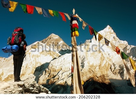 evening view of Everest with tourist and buddhist prayer flags from kala patthar and blue sky - way to Everest Base Camp - Nepal  - stock photo