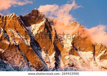 evening view of Lhotse and clouds on the top - way to mount Everest base camp - Nepal, warm tone - stock photo