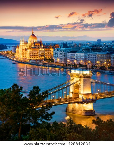 Evening view of Parliament and Chain Bridge in Pest city. Colorful sanset in Budapest, Hungary, Europe. Artistic style post processed photo. - stock photo