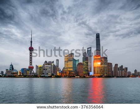 Evening view of Pudong skyline (Lujiazui) across the Huangpu River in Shanghai, China. Skyscrapers of downtown on waterfront. The Shanghai Tower of city business center is visible at right.
