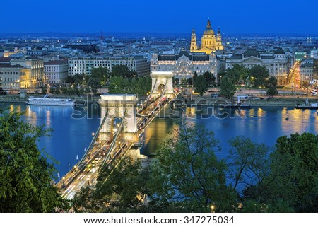 Evening view of Szechenyi Chain Bridge over Danube and St. Stephen's Basilica in Budapest, Hungary. View from Royal Palace in Buda Castle. - stock photo