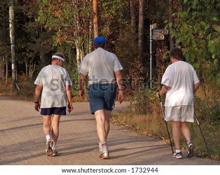 Evening walk using walking sticks - stock photo