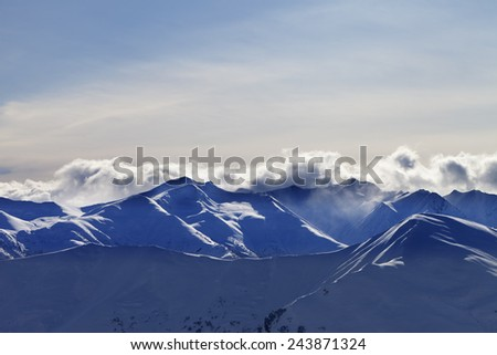 Evening winter mountains and sunlight clouds. Caucasus Mountains, Georgia. View from ski resort Gudauri. - stock photo