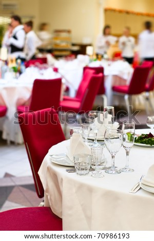 Events preparation for dinner, table appointment, unrecognizable waiters on background - stock photo