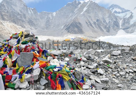 EVEREST BASE CAMP, NEPAL - CIRCA APRIL 2016: Everest Base Camp sign with stones, buddhist prayer flags and tents of climbers from everest expeditions.