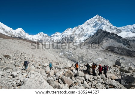Everest region, Nepal - Oct. 13, 2010: Unidentified tourists hiking in Everest region of Nepal, with the beautiful himalayas in background.