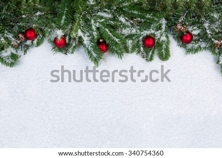 Evergreen branches and red ornaments covered in snow. Christmas concept with plenty of copy space.  - stock photo